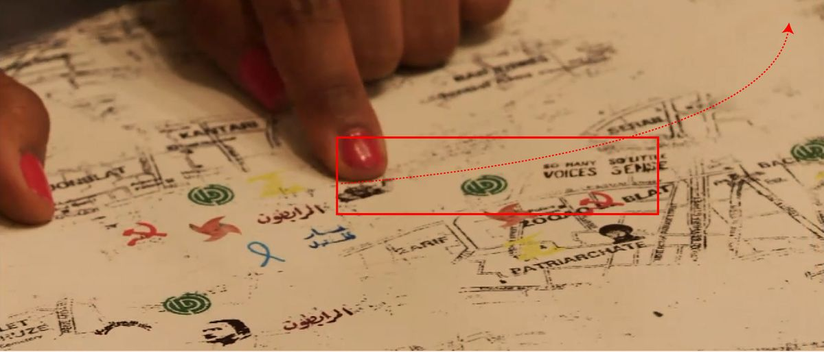 Tala Saleh's finger pointing to a design map of Beirut with political logos